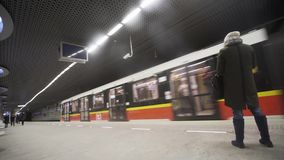 未知的到达回旋曲ONZ地铁车站的少妇和火车 华沙,波兰 图库摄影