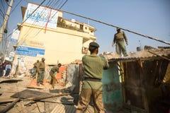 未知的尼泊尔警察在住宅贫民窟的爆破的操作时 库存图片