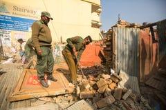 未知的尼泊尔警察在住宅贫民窟的爆破的操作时 免版税库存图片