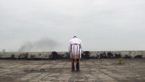 未知的非洲医生的背面图坐与书的椅子 他基于屋顶上面老 影视素材