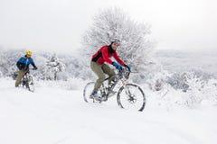未知的骑自行车的人在一个多雪的风景的冬天 免版税库存图片