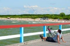 未知的年轻人从码头钓鱼在帕兰加,立陶宛 免版税库存照片