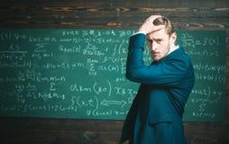 未经证明的定理 人礼服经典衣服看起来聪明,黑板背景 天才遭受未解决的数学 免版税库存照片