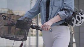 未被认出的年轻带领她的自行车的白色牛仔裤的体育亭亭玉立的可爱的白肤金发的妇女在的商店窗口附近 股票录像