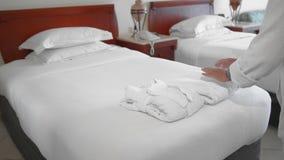 未被认出的成人资深妇女在一张床上的一件白色浴巾旁边投入并且调直一块完全白色毛巾在a 股票录像