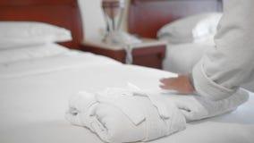 未被认出的成人资深妇女在一张床上的一件白色浴巾旁边投入并且调直一块完全白色毛巾在a 股票视频