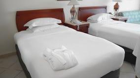 未被认出的成人资深妇女在床上的一件白色长袍旁边投入并且调直一块完全白色毛巾 ?treadled 股票录像