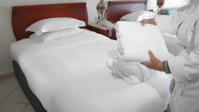 未被认出的成人资深妇女在床上的一件白色长袍旁边投入并且调直一块完全白色毛巾 ?treadled 股票视频