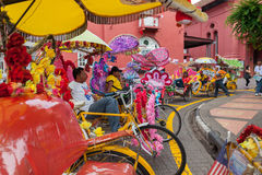 未认出的人乘驾trishaw,在路的一辆开花的车 库存图片