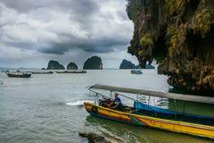 未认出的人在他的小船驾驶运输在Phang Nga国家公园的游人,泰国 免版税图库摄影