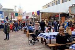 未认出的人民放松并且吃在室外街道F的地方食物 免版税库存图片