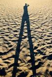 未认出的人的阴影一个海滩的在锡弗诺斯岛海岛,希腊 库存照片