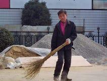 未认出的劳方在唐山,中国清扫有一把竹笤帚的一条街道 免版税库存图片