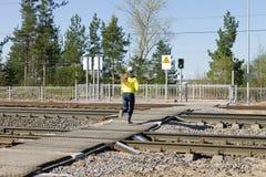 未认出的在一条行人交叉路的女孩连续铁路在一个绿色红绿灯发信号 免版税库存照片