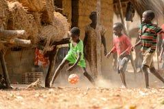 未认出的地方男孩踢在橙色海岛上的橄榄球 库存照片