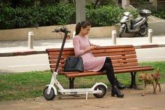 未认出的妇女坐与手机和电滑行车的一条长凳 免版税库存图片
