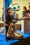 未认出的妇女站立近的机器人 图库摄影