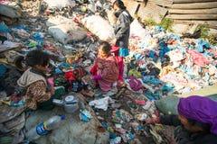 未认出的孩子和他的父母在午餐期间在断裂在工作在转储, 2013年12月24日之间在KTM,尼泊尔 免版税库存照片