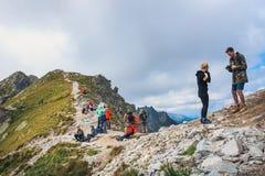 未认出的小组远足者休息和被用尽在高Tatra Mountai的Krzyzne通行证 图库摄影