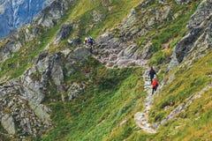 未认出的小组远足者休息和被用尽在高Tatra Mountai的Krzyzne通行证 免版税库存图片
