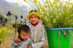 未认出的少数族裔哄骗与油菜籽花篮子在Hagiang,越南 免版税图库摄影