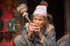 未认出的尼泊尔人画象在街道上抽烟 免版税库存图片