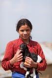 年轻未认出的尼泊尔女孩画象有孩子山羊的 库存照片