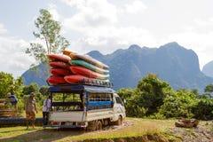未认出的旅游帮助的汽车在泥黏附了在路 免版税库存照片
