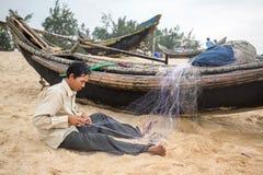 未认出的渔夫repairin捕鱼网,越南 免版税图库摄影