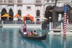 未认出的游人在大运河享受长平底船乘驾在威尼斯式度假旅馆赌博娱乐场 库存图片