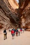 未认出的游人审阅Petra的峡谷,约旦 免版税库存图片