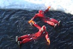未认出的游人适应与生存衣服冰游泳在冻波罗的海 免版税库存照片