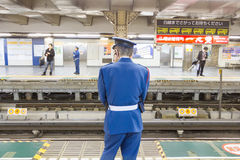 未认出的火车官员等待地铁在东京 库存照片