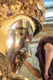 未认出的缅甸修士清洗菩萨雕象与金黄纸在Mahamuni菩萨寺庙, 8月 免版税库存图片
