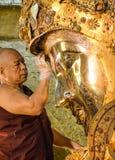 未认出的缅甸修士清洗菩萨雕象与金黄纸在Mahamuni菩萨寺庙, 8月 免版税图库摄影