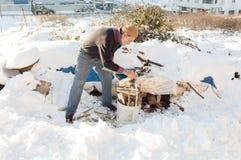 未认出的老土耳其人在塑料桶投入切好的火森林 免版税库存图片