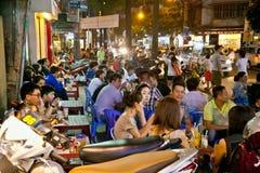 未认出的青年时期享用在西贡` s夜生活中的一个小组, 免版税库存照片