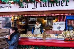未认出的面包师在圣诞节市场上在巴黎 免版税库存照片