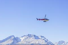 未认出的直升机飞行在惊人的西海岸的,南岛,新西兰 库存照片