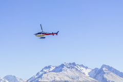 未认出的直升机飞行在惊人的西海岸的,南岛,新西兰 免版税库存照片