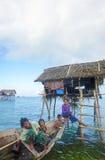 未认出的Bajau Laut在一条小船哄骗在2015年11月19日的马伊加海岛 免版税图库摄影