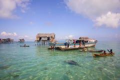 未认出的Bajau Laut在一条小船哄骗在2015年11月19日的马伊加海岛 免版税库存照片