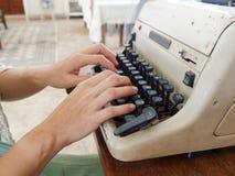 未认出的person's递键入在减速火箭的打字机 库存图片