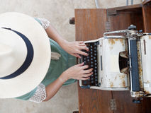 未认出的woman's递键入在减速火箭的打字机 库存照片