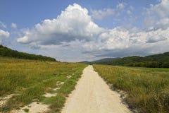 未铺砌的土路采取对与云彩的天空 免版税库存照片