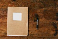 未贴标签的学报和一支笔在木桌上 库存图片