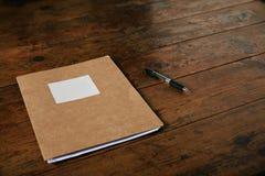 未贴标签的学报和一支笔在木桌上 免版税库存图片