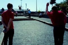 本地人演奏petanque的人在午休时间期间在一个公园 图库摄影