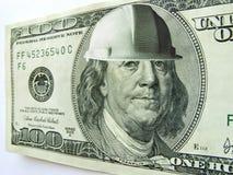本富兰克林一百元钞票佩带的建筑安全帽 免版税图库摄影