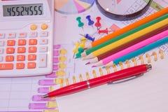 本文绘了五颜六色的图表 在谎言上笔、铅笔、放大器和计算器 免版税库存图片